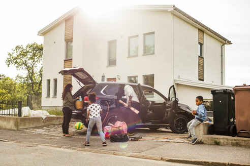 Family with electric car on driveway against house - MASF11426