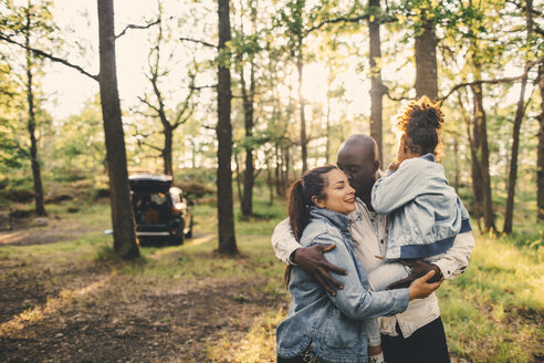 Family standing against trees in park during sunset - MASF11438