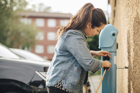 Side view of woman adjusting electric plug for charging car at station - MASF11450