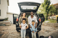 Portrait of smiling multi-ethnic family leaning on car trunk in front yard - MASF11453