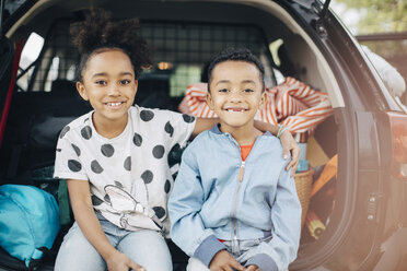 Portrait of smiling girl sitting with arm around on brother in electric car trunk - MASF11456