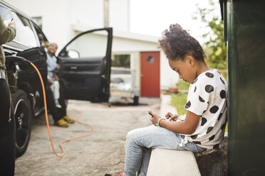 Side view of girl using smart phone while sitting in front yard - MASF11462