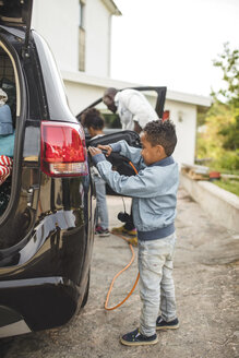 Full length of boy charging electric car while standing on driveway - MASF11465