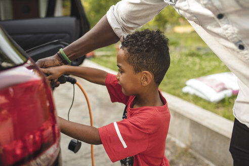 Midsection of man assisting son in charging electric car on driveway at front yard - MASF11468