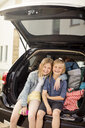Portrait of smiling siblings sitting in car trunk against house - MASF11471