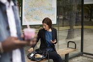 Businesswoman eating sandwich while sitting at bus stop in city - MASF11477
