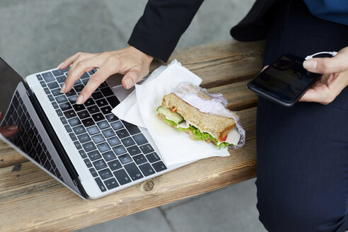 Midsection of businesswoman using laptop while sitting with smart phone and sandwich at bus stop in city - MASF11495