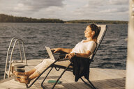 Full length of woman relaxing on deck chair at jetty over lake - MASF11510
