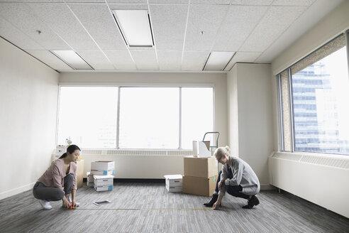 Businesswomen with tape measure measuring floor space in new office - HEROF23663