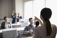 Businesswoman with microphone answering audience questions in office classroom - HEROF23681