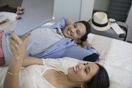 Couple using digital tablet on bed - HEROF23771