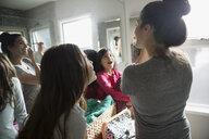 Daughters watching mother applying makeup in bathroom mirror - HEROF23786