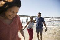 Couple walking on sunny beach - HEROF23801