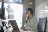 Businesswoman working at laptop in office - HEROF23825