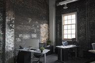 Desks at brick wall in empty loft creative office - HEROF23882