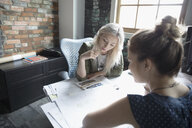 Female architects reviewing blueprints in office - HEROF23894