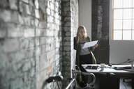 Creative businesswoman talking on smart phone and reviewing paperwork at brick wall in office - HEROF23906