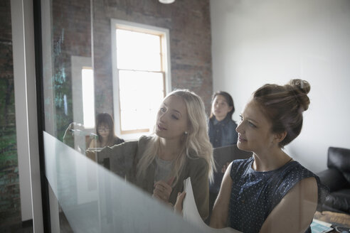 Female architects meeting, reviewing blueprint in office - HEROF23909