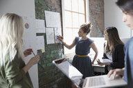 Creative businesswoman leading meeting, explaining paperwork in office - HEROF23912