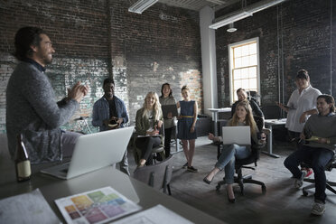 Creative business people with laptops meeting in open plan loft office - HEROF23921