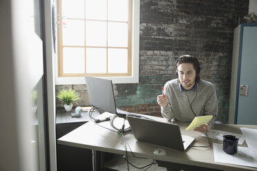 Creative businessman talking on telephone with headset at laptop in office - HEROF23930
