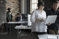 Creative business people working, meeting in open plan office - HEROF23975
