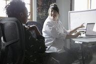 Creative businesswomen talking, working at computer in office - HEROF23981