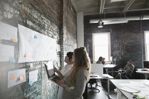 Creative businesswomen talking, discussing proofs hanging on wall in office - HEROF23996