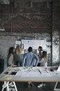Creative business people brainstorming at brick wall in open plan loft office - HEROF24002