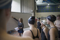 Female coach at whiteboard coaching swimming team at practice - HEROF24017