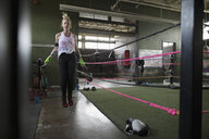 Female boxer jumping rope next to boxing ring - HEROF24029