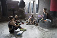 Female boxers resting, eating snack post workout at gritty gym with punching bags - HEROF24038