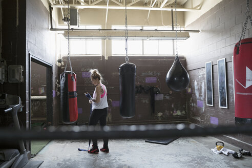 Female boxer wrapping wrist at punching bag in gritty gym - HEROF24041