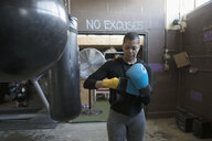 Female boxer putting on boxing gloves at punching bag in gritty gym - HEROF24050