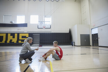Female coach coaching male basketball player in college gymnasium - HEROF24077