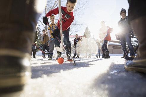 Boys playing ice hockey in sunny, snowy driveway - HEROF24116