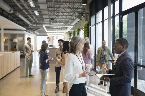 Business people networking in office lobby - HEROF24188