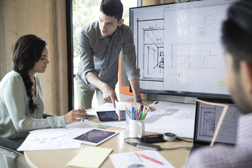 Architects reviewing digital blueprints in conference room meeting - HEROF24206