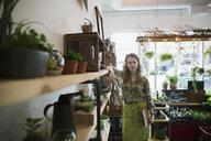 Portrait of terrarium shop owner leaning on shelf - HEROF24296