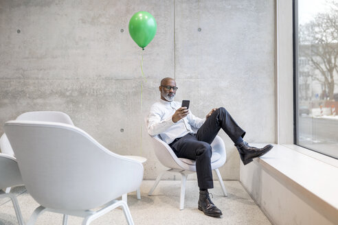 Mature businessman with green balloon sitting on armchair looking at cell phone - FMKF05355