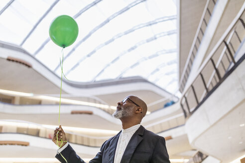 Mature businessman with green balloon - FMKF05364