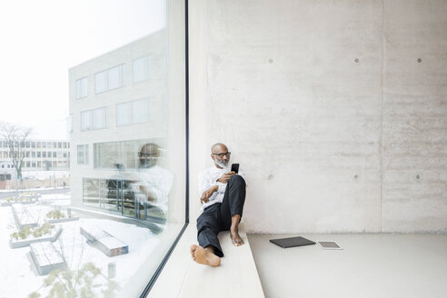 Barefoot mature businessman sitting on window sill using smartphone - FMKF05373