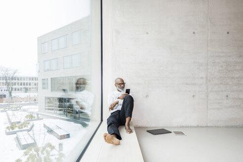 Barefoot mature businessman sitting on window sill using smartphone - FMKF05373