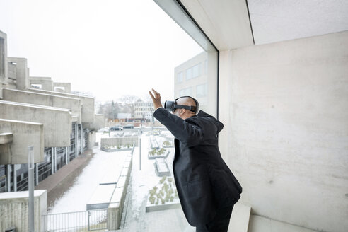 Mature businessman with Virtual Reality Glasses looking out of window - FMKF05376