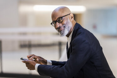 Portrait of smiling mature businessman with cell phone - FMKF05400