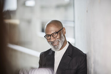 Portrait of smiling mature businessman with grey beard wearing glasses - FMKF05406