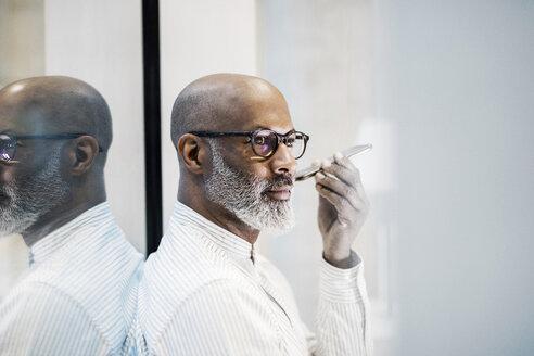 Portrait of bald mature businessman with grey beard using smartphone - FMKF05412