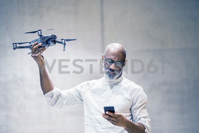 Portrait of bald mature man holding quadcopter while looking at cell phone - FMKF05418 - Jo Kirchherr/Westend61