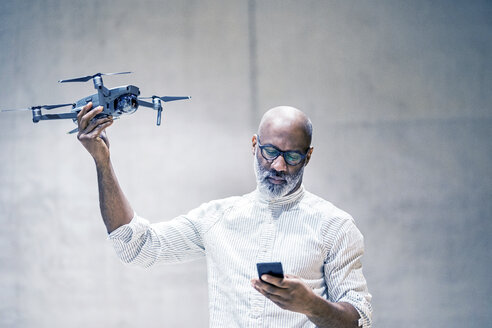 Portrait of bald mature man holding quadcopter while looking at cell phone - FMKF05418