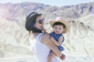 USA, California, Death Valley National Park, Twenty Mule Team Canyon, happy mother and baby girl - GEMF02843